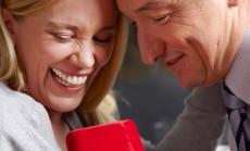 Mann macht einer lachenden Frau einen Heiratsantrag mit Ring