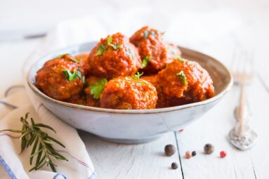 Homemade meatballs with tomato sauce and parsley in a bowl