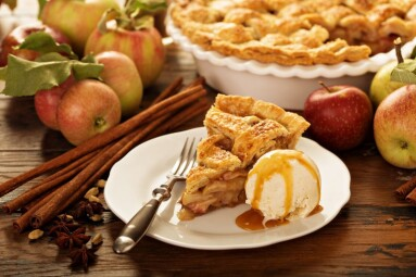 Piece of an apple pie with ice cream on a plate