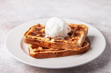 Belgian waffles with ice cream on a white plate. Homemade waffer craft background.