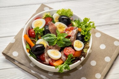 Close up. French cuisine. Traditional niçoise (nicoise) salad in a white plate on a polka dot napkin. White background.