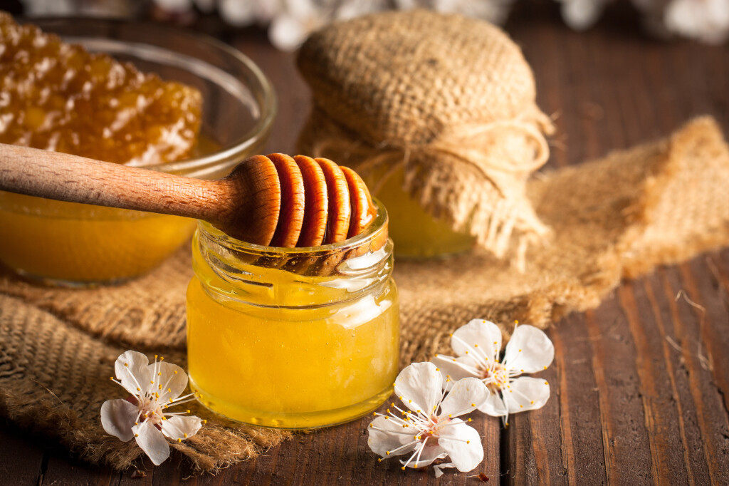 Honey,Dripping,From,A,Wooden,Honey,Dipper,In,A,Jar